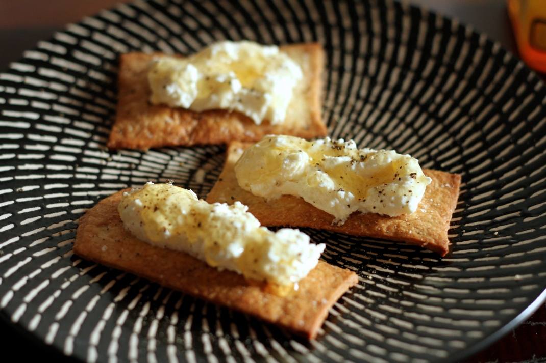 Crackers topped with homemade ricotta, honey and black pepper