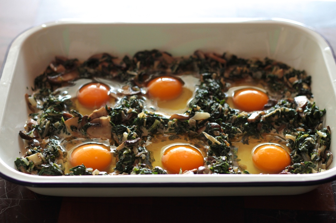Baked eggs with greens and mushrooms