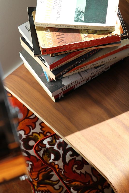A pile of second hand books, Matt Blatt coffee table and retro cushions