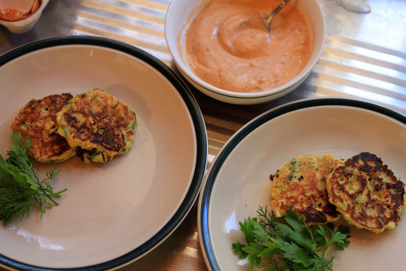 Plating up sweetcorn fritters and harrissa sauce