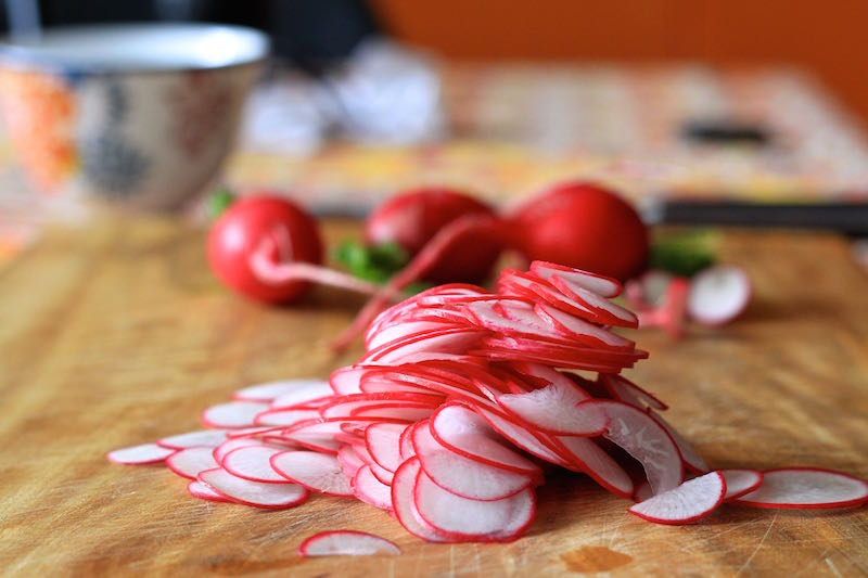 Red radishes sliced using a mandolin, ready to make pickle